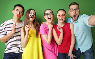Happy friends with party decor taking selfie on color background