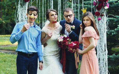 elegant stylish happy guests and bride and groom having funny photos on the background of arch